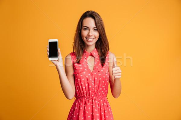 Smiling brunette woman in dress showing blank smartphone screen Stock photo © deandrobot