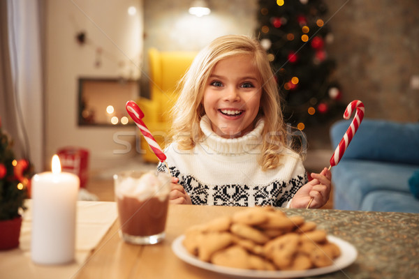 Happy exited little girl in knitted sweater holding two candy ca Stock photo © deandrobot