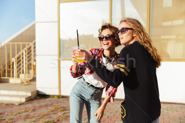 Two happy teenage girls in sunglasses toasting Stock photo © deandrobot
