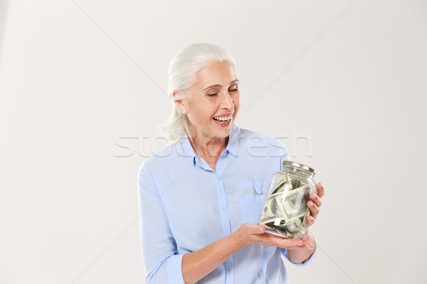 Happy senior lady with closed eyes holding glasses bank with dol Stock photo © deandrobot