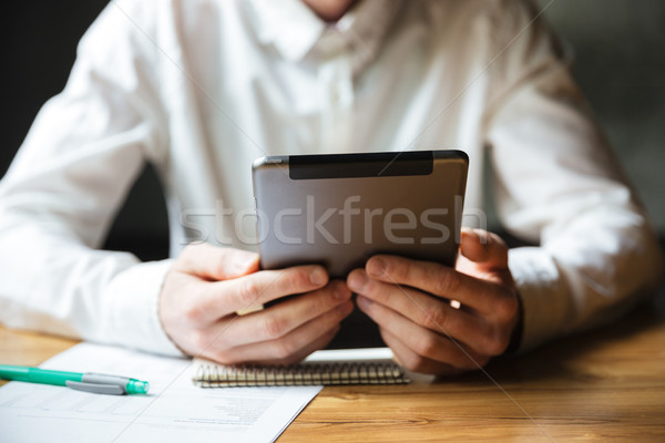 Cropped photo of man in white shirt using digital tablet Stock photo © deandrobot