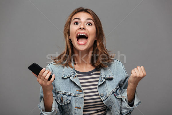Overjoyed girl in jeans jacket holding mobile phone and showing  Stock photo © deandrobot
