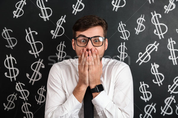 Close-up portrait of shocked man in glasses covering his mouth,  Stock photo © deandrobot