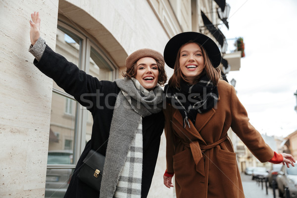 Portrait of two cheery girls dressed in autumn clothes walking Stock photo © deandrobot