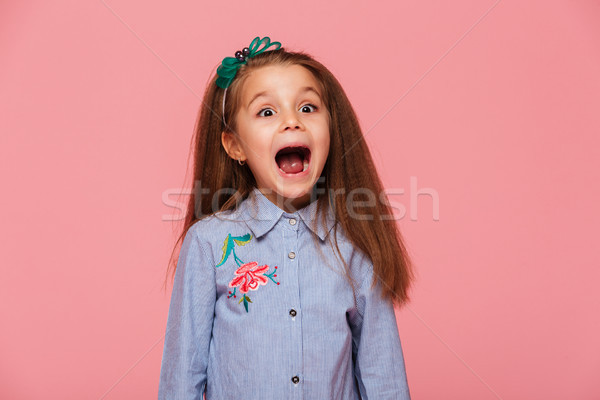 Joyous female kid in trendy shirt having fun shouting being exci Stock photo © deandrobot