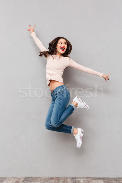 Full-length image of cheerful female in jeans jumping with arms  Stock photo © deandrobot