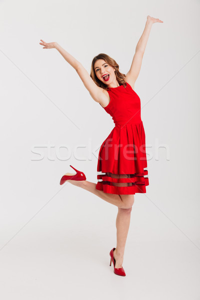 Full length portrait of a cheerful petty girl Stock photo © deandrobot