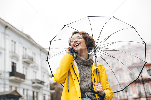 Shot of young woman in yellow raincoat and glasses talking on mo Stock photo © deandrobot
