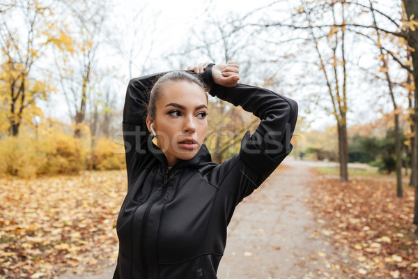 Portrait of a confident fitness girl in earphones Stock photo © deandrobot
