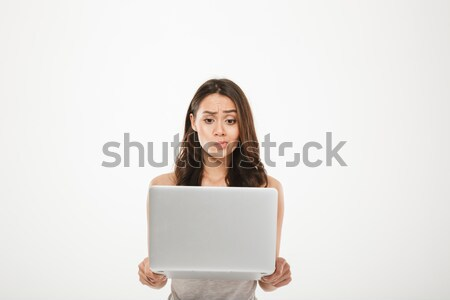 Image of young woman 30s looking on screen of her silver noteboo Stock photo © deandrobot