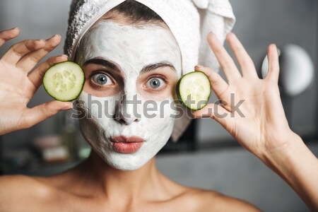 Stock photo: Attractive smiling lady with scrab on face holding cucumber slices isolated