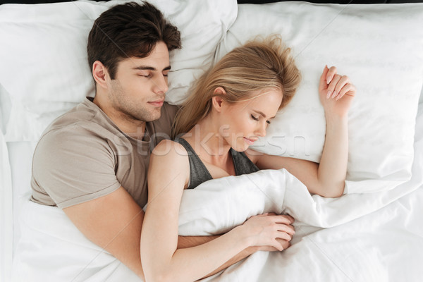 Portrait of calm handsome couple sleeping in bed Stock photo © deandrobot