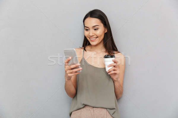 Portrait of a smiling asian woman holding takeaway coffee Stock photo © deandrobot
