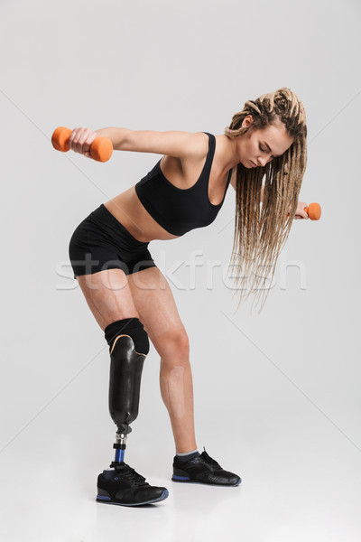 Stock photo: Healthy young disabled sportswoman make exercises with dumbbells.