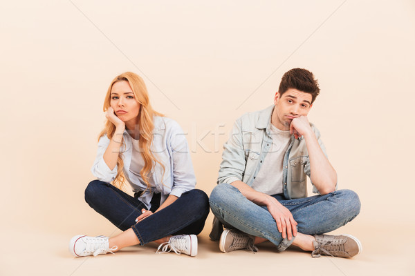 Image of dissatisfied man and woman sitting on the floor with le Stock photo © deandrobot