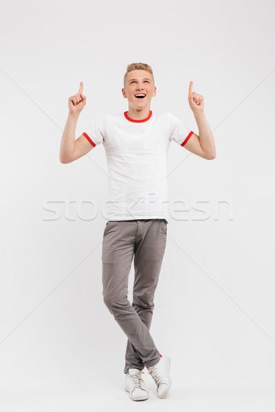Teljes alakos portré derűs tizenéves fiú mutat felfelé Stock fotó © deandrobot