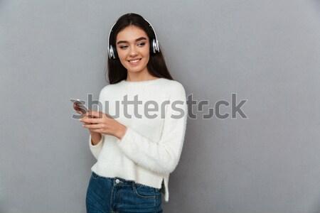 улыбаясь брюнетка женщину свитер прослушивании Сток-фото © deandrobot