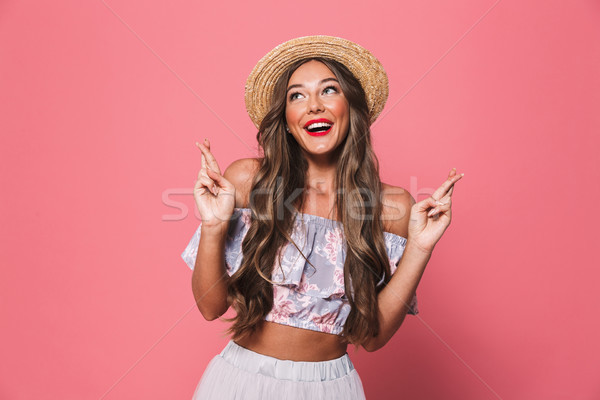 Image of charming young lady in straw hat holding fingers crosse Stock photo © deandrobot