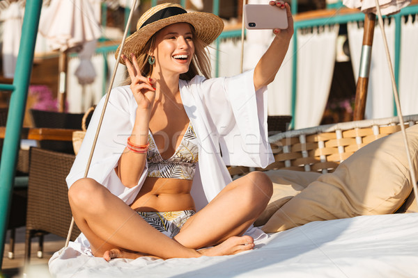 Photo of happy woman 20s in straw hat and swimsuit smiling and t Stock photo © deandrobot