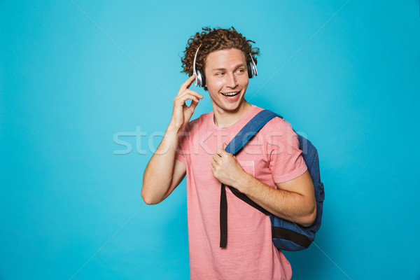 Portrait of attractive man 18-20 with curly hair wearing backpac Stock photo © deandrobot