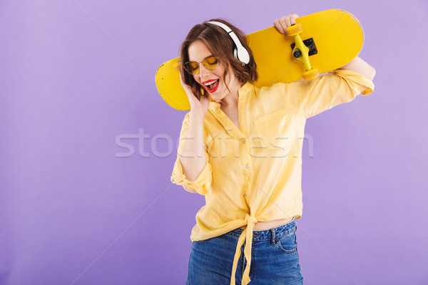 Portrait of a delighted young girl in headphones Stock photo © deandrobot