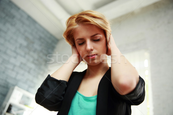 Portrait of a pensive woman touched her head with closed eyes Stock photo © deandrobot