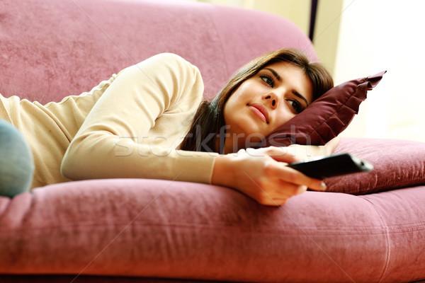Fiatal gyönyörű nő kanapé távirányító otthon lány Stock fotó © deandrobot