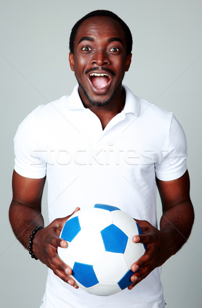 Funny african man holding soccer ball on gray background Stock photo © deandrobot