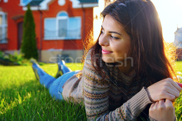 Happy woman lies on the lawn and looking away Stock photo © deandrobot
