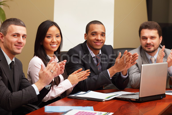 Multi ethnic business group greets you with clapping and smiling. Focus on asian woman Stock photo © deandrobot