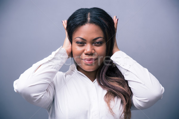 African businesswoman covering her ears Stock photo © deandrobot