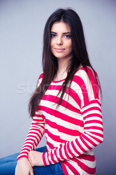 Portrait of attractive young woman over gray background Stock photo © deandrobot