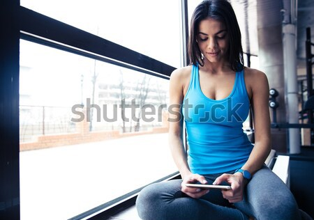 Smiling fit woman talking on the phone Stock photo © deandrobot