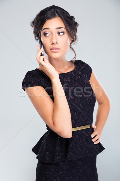 Stock photo: Woman in black dress talking on the phone