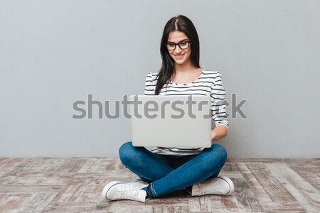 Casual woman sitting on the floor with laptop Stock photo © deandrobot