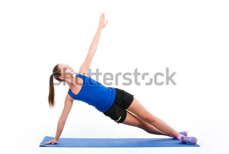 Young sportswoman in sportwear doing yoga Stock photo © deandrobot