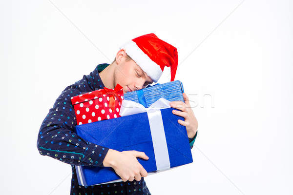 Amusing cute man in santa claus hat hugging gift boxes  Stock photo © deandrobot