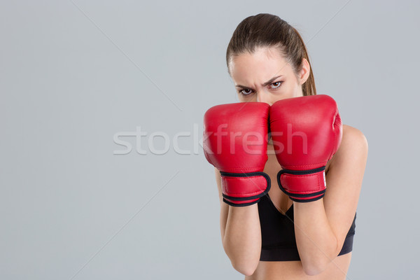Strong intense fitness woman covered her face with boxing gloves  Stock photo © deandrobot