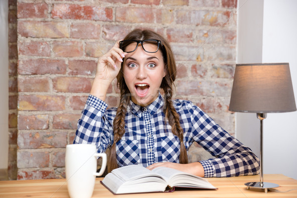 Excited woman sitting at the table with book Stock photo © deandrobot