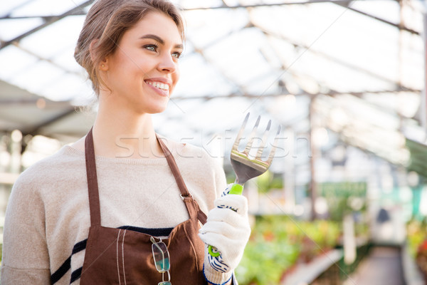 Cheerful woman gardener holding fork for transplantation plants in greenhouse Stock photo © deandrobot