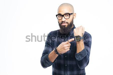 Hairless african man in glasses with beard pointing on watch Stock photo © deandrobot