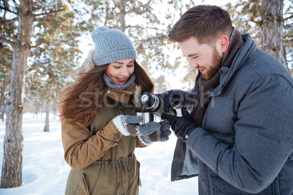 Happy couple drinking hot tea in winter park Stock photo © deandrobot
