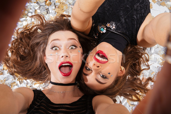 Two excited pretty women taking selfie and lying  Stock photo © deandrobot