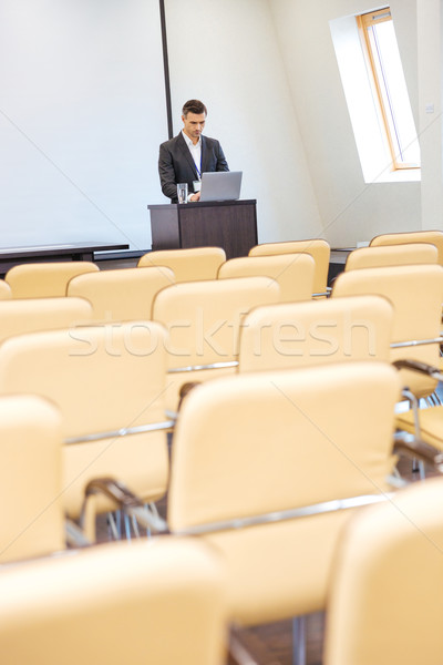 Pensive businessman standing and using laptop in empty meeting hall Stock photo © deandrobot
