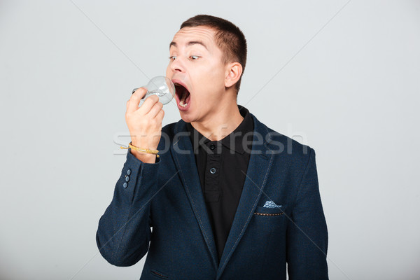 Man trying to eat bulb Stock photo © deandrobot