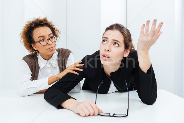 Pretty african american businesswoman supporting her upset despaired colleague Stock photo © deandrobot