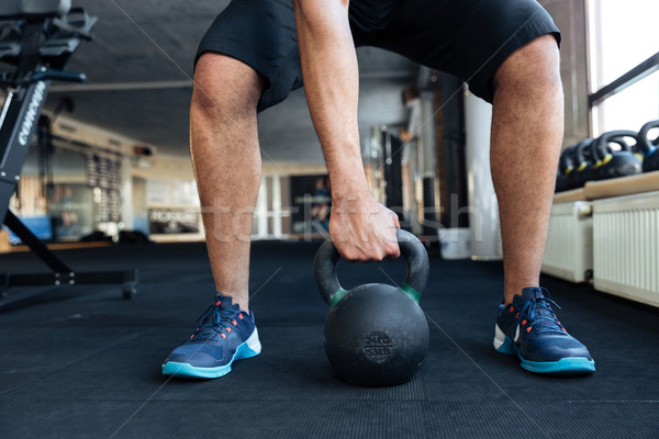 Stock photo: Bodybuilder using kettlebell in his workout at the gym