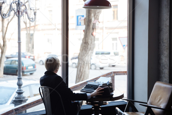 Blonde girl sitting backwards in a cafe Stock photo © deandrobot