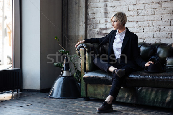 Stylish blonde girl sitting on the couch  Stock photo © deandrobot