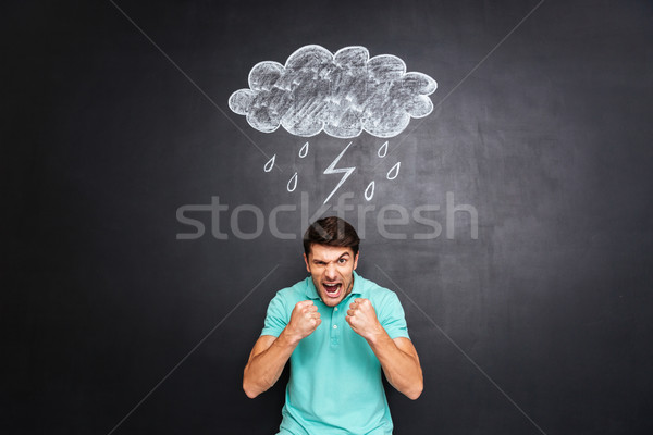 Angry young man yelling over background of chalkboard Stock photo © deandrobot